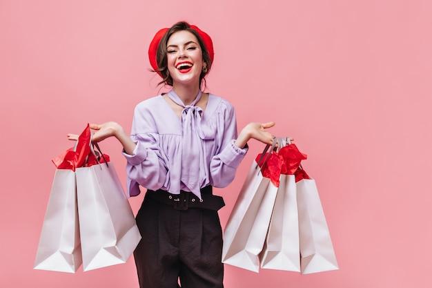 Frau in der guten stimmung lacht und hält pakete nach dem einkaufen auf rosa hintergrund.