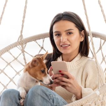 Frau in der hängematte mit ihrem hund und smartphone