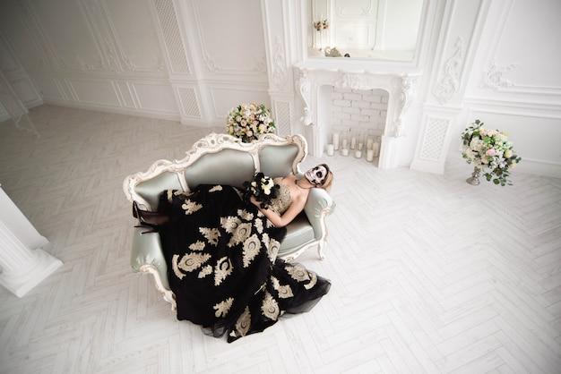 Frau in der halloween-ruhe. eine frau mit totenkopf schminken