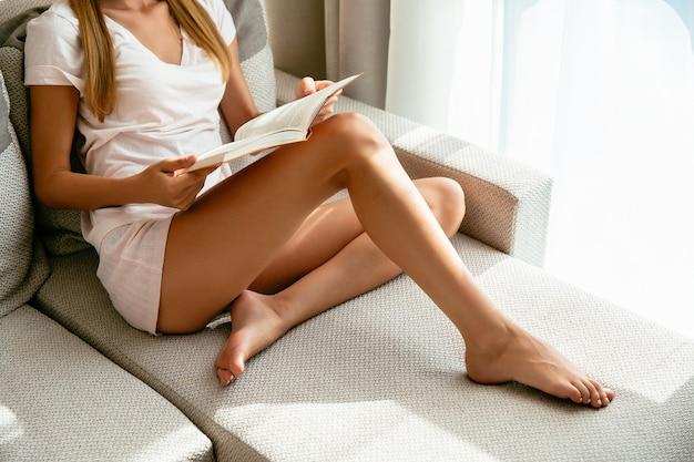 Frau in der hauptkleidung, die zu hause auf sofa und lesebuch sitzt