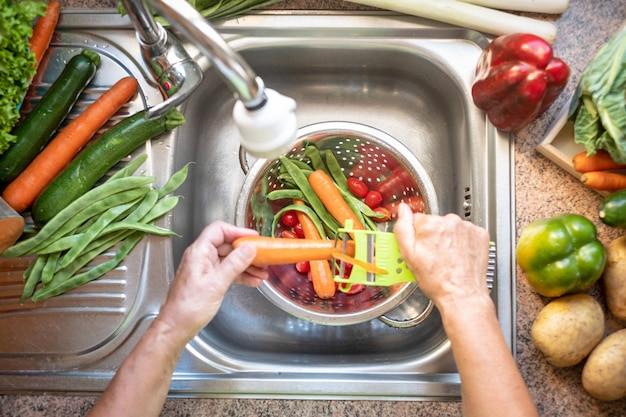 Frau in der heimischen küche, die gemüse unter fließendem wasser wäscht, eine karotte schälen