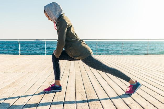 Frau in der jacke und in der haube, die morgens sportübungen auf dem strand tun