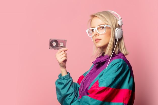 Frau in der kleidung der 90er jahre mit kopfhörern und audiokassette