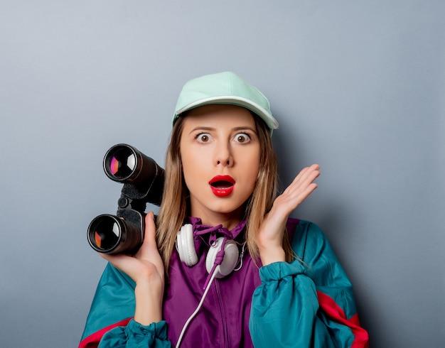 Frau in der kleidungsart der 90er jahre mit ferngläsern