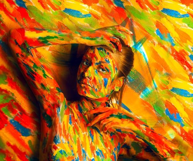 Frau in der körperartfarbe nahe der mehrfarbigen wand