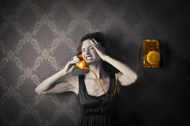 Frau in der krise, die an einem klassischen telefon spricht