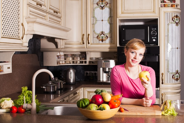 Frau in der küche bereitet sich ein abendessen vor und isst einen apfel. konzept für gesunde ernährung