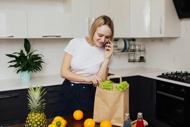 Frau in der küche, die am telefon spricht und gemüse und obst in der papiertüte betrachtet