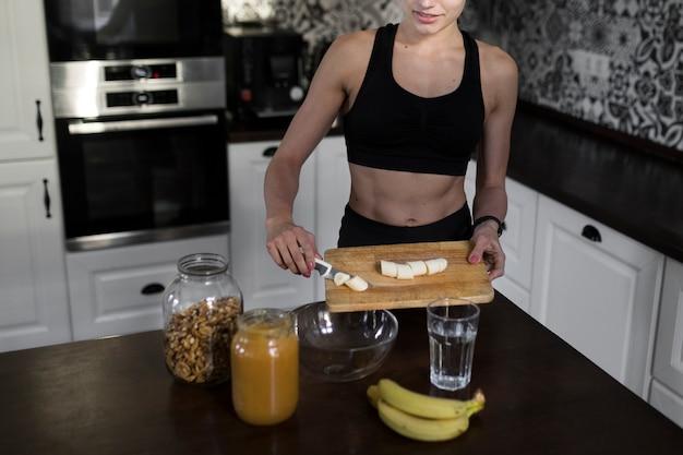 Frau in der küche, die eine gesunde mahlzeit vorbereitet