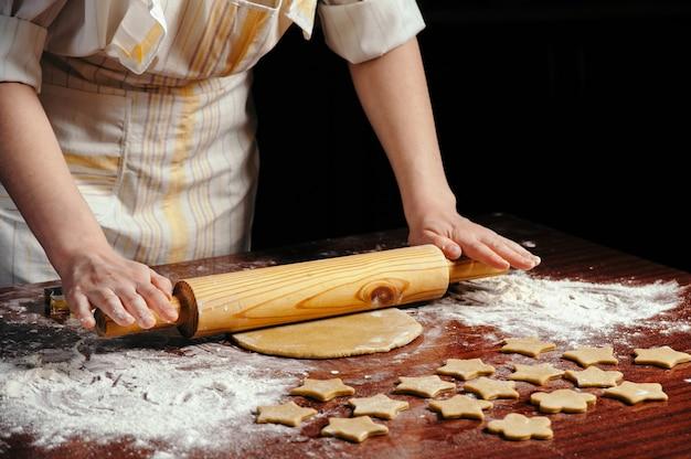 Frau in der küche, die einen teig auf einem holztisch mit einem hölzernen nudelholz rollt