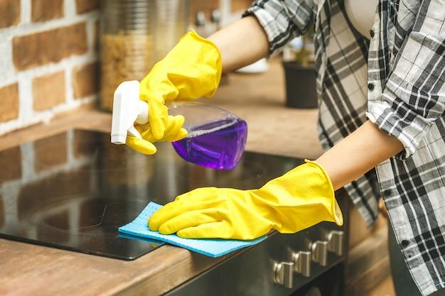 Frau in der küche, die staub mit einem spray und einem staubtuch abwischt, während sie ihr haus putzt, nahaufnahme