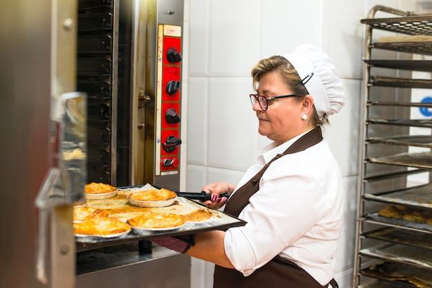 Frau in der küche einer bäckerei kocht kuchen in einem ofen