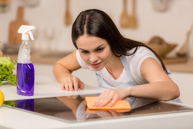 Frau in der küche lächelt und wischt staub mit einem spray und einem staubtuch ab, während sie ihr haus putzt, nahaufnahme