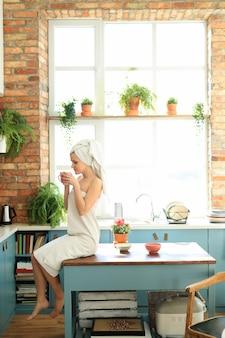 Frau in der küche mit handtuch auf dem kopf nach der dusche