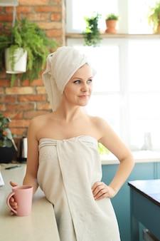 Frau in der küche mit handtuch, das ihren körper nach dem duschen bedeckt