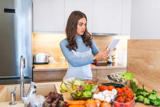 Frau in der küche nach rezept auf digital-tablet