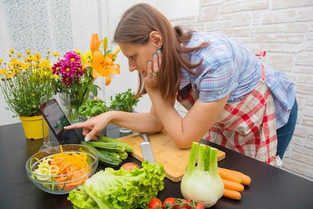 Frau in der küche nach rezept auf digitaler tablette