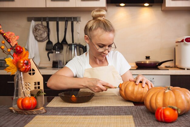 Frau in der küche schnitzt einen kürbis für halloween in einem raum mit herbstdekor und einem lampenhaus. gemütliches zuhause und vorbereitung auf halloween.