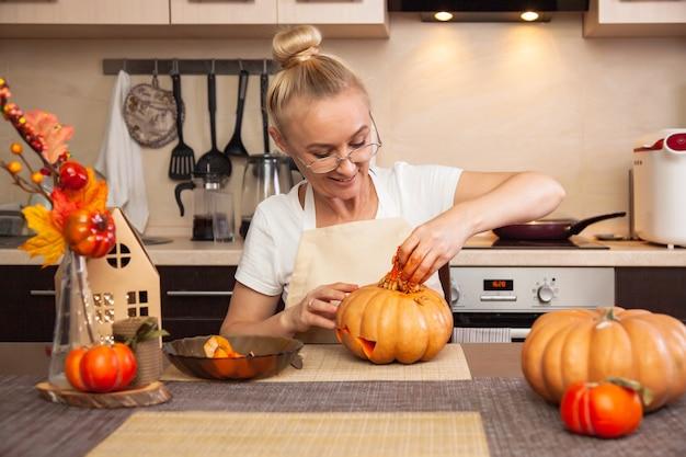 Frau in der küche zieht kürbiskerne für halloween in einem raum mit herbstdekor und einem lampenhaus aus. gemütliches zuhause und vorbereitung auf halloween