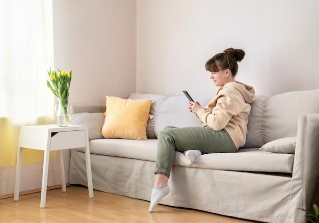 Frau in der leuchtend gelben bluse, die auf sofa sitzt