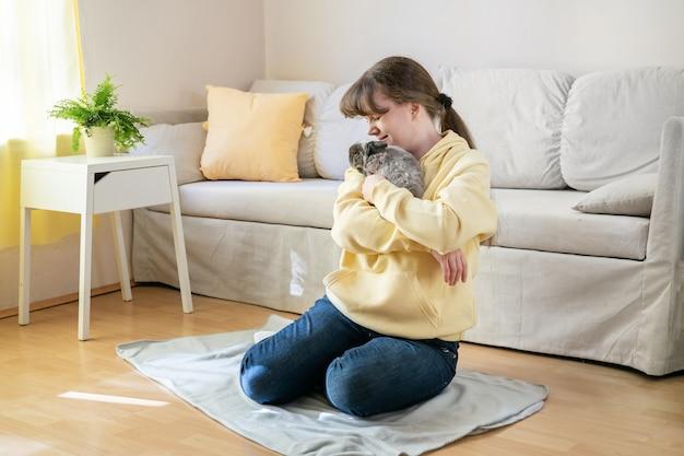 Frau in der leuchtend gelben bluse, die niedliches graues kaninchen zu hause hält
