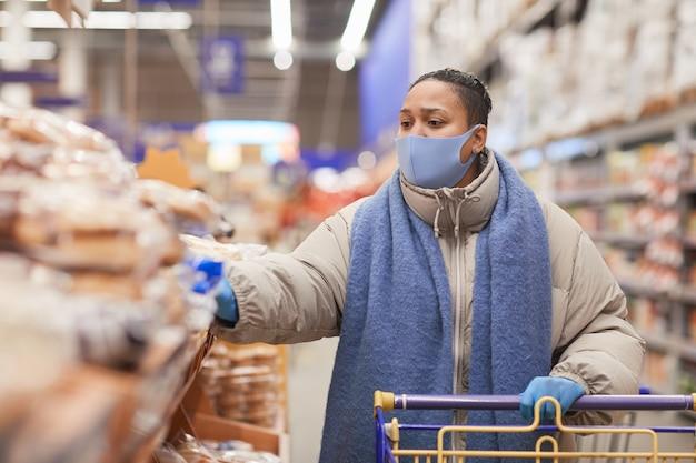 Frau in der maske, die mit einkaufswagen entlang der regale im lebensmittelgeschäft geht