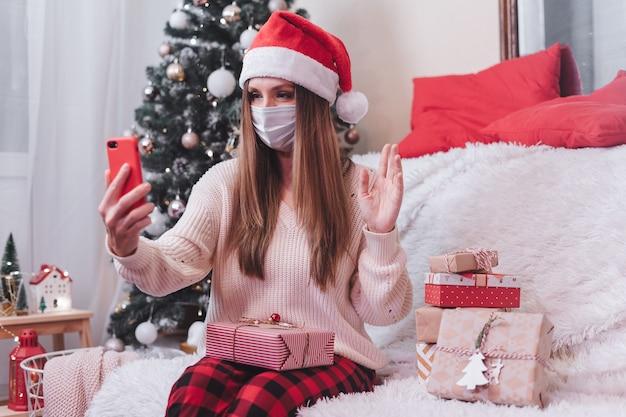 Frau in der maske mit weihnachtsgeschenk, die einen videoanrufanruf auf mobiltelefon hat