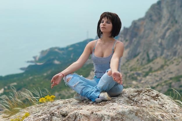 Frau in der meditation, die sich auf dem felsen entspannt