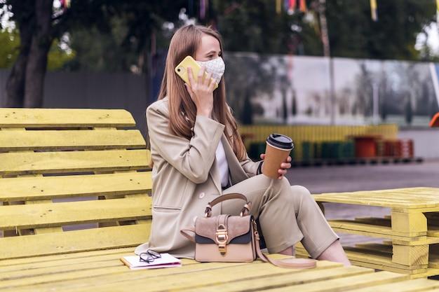 Frau in der medizinischen gesichtsmaske, die über das telefon spricht