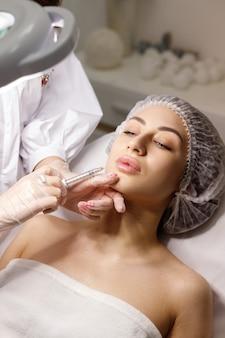 Frau in der medizinischen kappe macht einen schuss in die lippen einer kosmetikerin