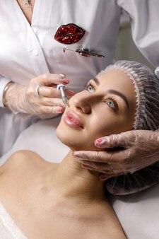 Frau in der medizinischen kappe mit lippenschuss auf kosmetikerin