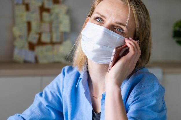 Frau in der medizinischen maske arbeitet büroarbeit entfernt von zu hause auf küche. handy sprechen. computer benutzen. online-fernunterricht und arbeit.