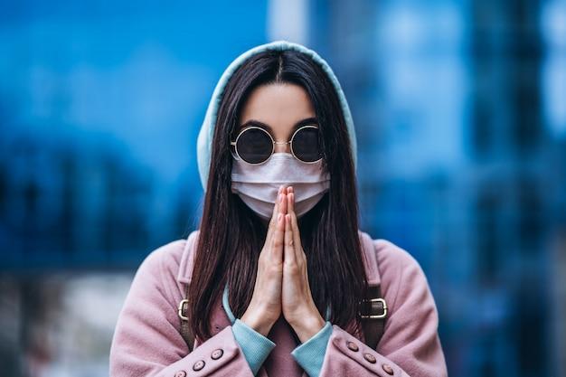 Frau in der medizinischen maske, die draußen in der leeren stadt betet. gesundheitsschutz und prävention von virusausbruch, coronavirus, covid-19, epidemie, pandemie, infektionskrankheiten, quarantänekonzept