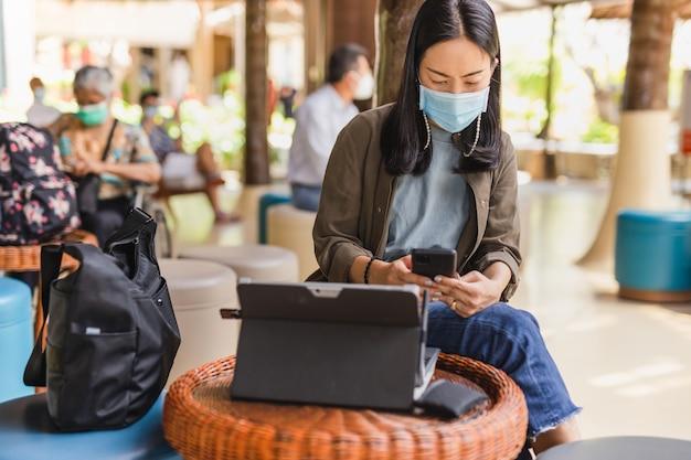 Frau in der medizinischen maske, die handy und laptop in der flughafenlobby verwendet.