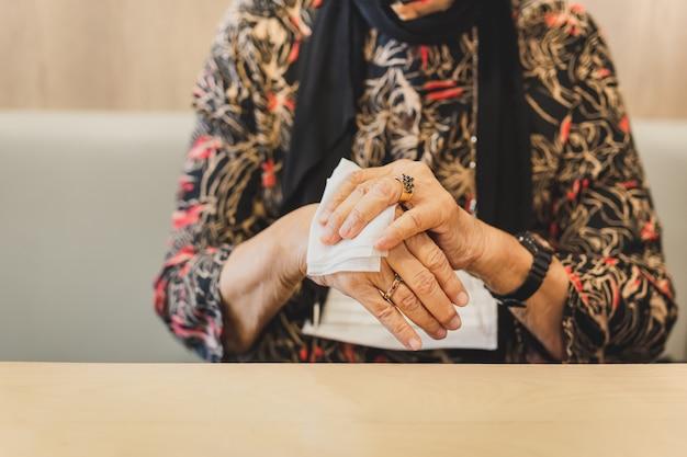 Frau in der medizinischen maske, die ihre hände mit feuchten tüchern reinigt.