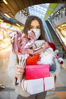 Frau in der medizinischen maske, die luftballons in form von zahlen im einkaufszentrum hält
