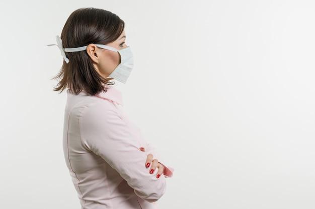 Frau in der medizinischen maske, die profil betrachtet