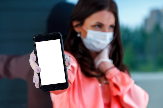 Frau in der medizinischen maske und in den einweghandschuhen mit telefon in der hand