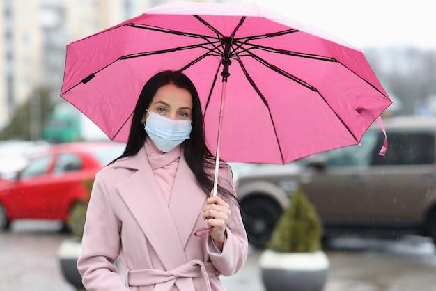 Frau in der medizinischen schutzmaske, die regenschirm in händen hält.