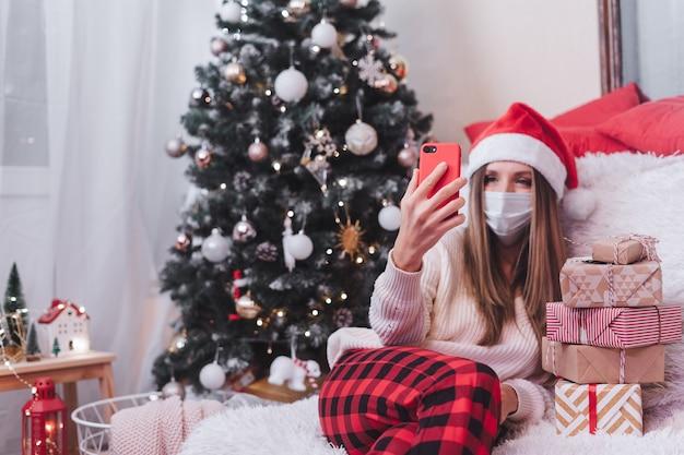 Frau in der medizinischen schutzmaske mit geschenkbox, die einen videoanruf-chat am smartphone hat