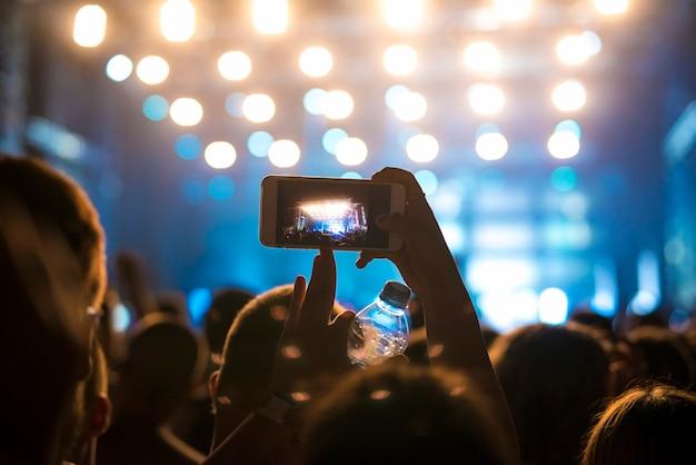 Frau in der menge, die foto der bühne am musikfestival macht