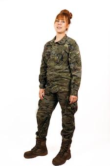 Frau in der militäruniform, die mit einem selbstbewussten lächeln steht