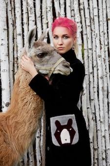 Frau in der nähe von lama im herbst an der wand von birken. kreatives helles rosa make-up auf dem mädchengesicht, haarfarbton. porträt eines mädchens mit einem lama. wandern im herbstlichen wald. herbstkleidung
