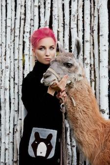 Frau in der nähe von lama im herbst auf dem hintergrund von birken. kreatives hellrosa make-up auf dem mädchengesicht, haarfärbung. porträt eines mädchens mit einem lama. wandern im herbstlichen wald. herbstkleidung