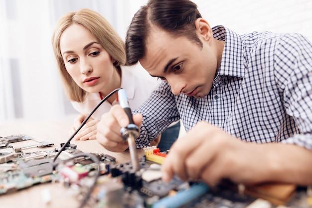 Frau in der nähe von meister mit lötlampe bewertungen technik