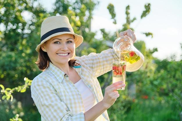 Frau in der natur, die glas der erdbeer- und minzlimonade hält
