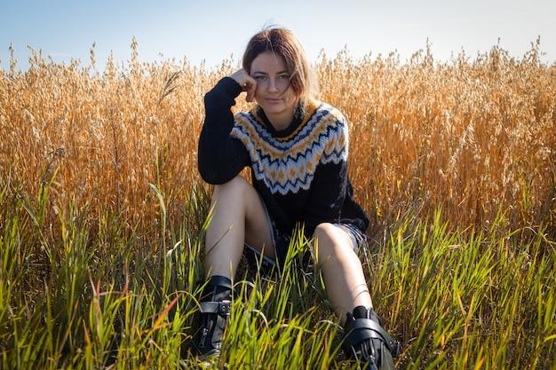 Frau in der natur posieren. junge frau in der stilvollen kleidung: gestrickte strickjacke, kleid und stiefel, die gegen den hintergrund des waldes, der straße und des feldes aufwerfen.