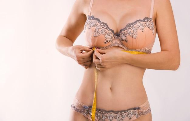Frau in der pfirsichfarbenen unterwäsche mit einem band