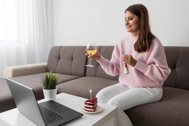 Frau in der quarantäne, die geburtstag mit freunden über laptop und getränk feiert