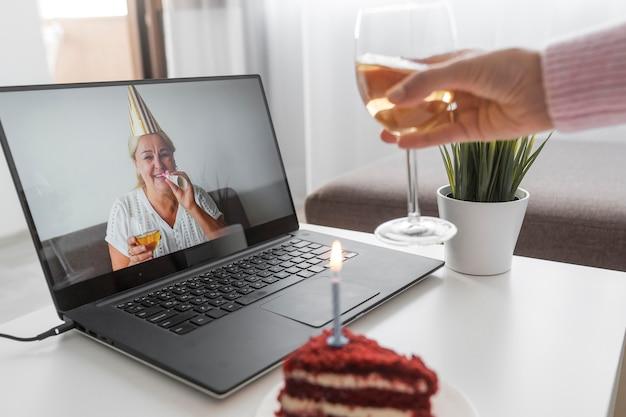 Frau in der quarantäne, die geburtstag mit freunden über laptop und kuchen feiert